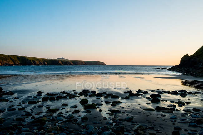 Beach and cliffs on Pembrokeshire Coast at sunset, Wales, UK. — Stock Photo