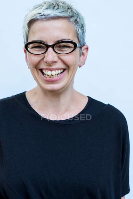 Woman with short grey hair wearing glasses smiling in camera. — Stock Photo