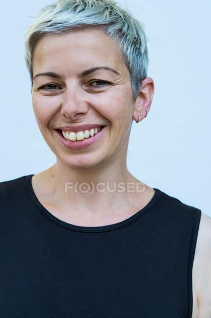Женщина с короткими седыми волосами в черном топе улыбается в камеру . — стоковое фото