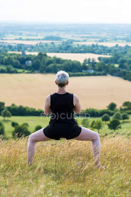Rear view of woman practicing outdoor yoga on hillside. — Stock Photo
