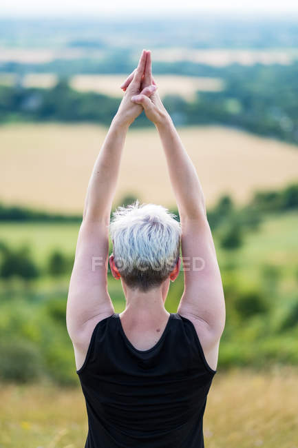 Vue arrière de la femme pratiquant le yoga en plein air sur la colline . — Photo de stock