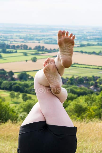 Ноги вверх женщины в открытом классе йоги на холме сельской местности . — стоковое фото