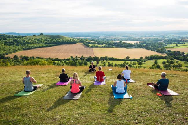 Група жінок і чоловіків, які беруть участь у класі йоги на схилі пагорба.. — стокове фото