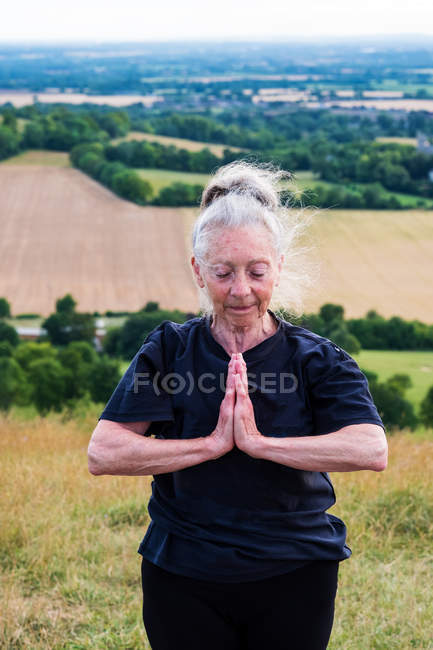 Senior woman taking part in outdoor yoga class on a hillside. — Stock Photo