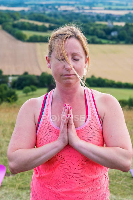 Mature woman taking part in outdoor yoga class on a hillside. — Stock Photo