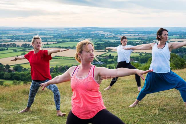 Група жінок, які беруть участь у класі йоги на схилі пагорба.. — стокове фото
