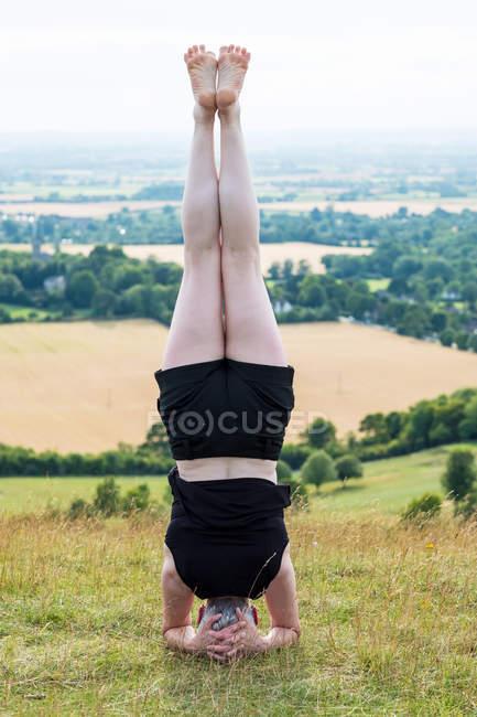 Вид сзади на женщину, участвующую в занятиях йогой на открытом воздухе на склоне холма . — стоковое фото
