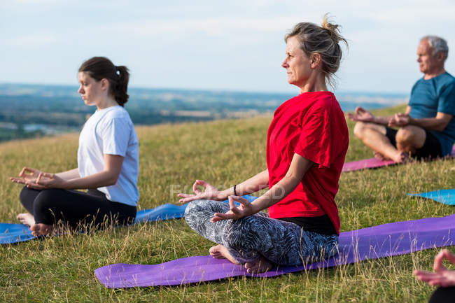 Group of women and man taking part in outdoor yoga class on a hillside. — Stock Photo