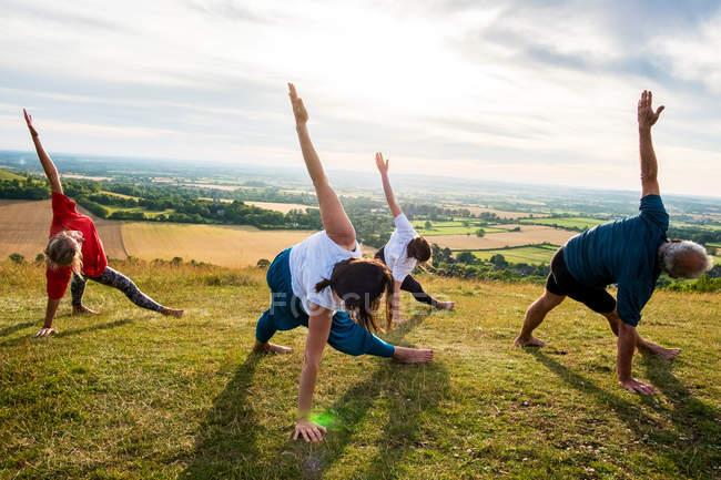 Група жінок і чоловіків, які беруть участь у відкритому класі йоги на схилі пагорба.. — стокове фото