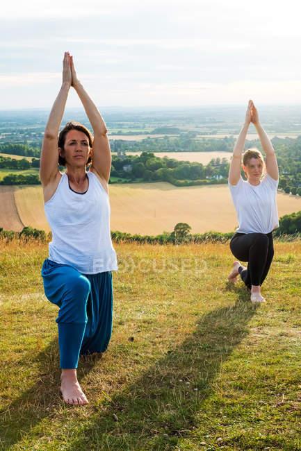 Deux femmes prenant part à un cours de yoga en plein air sur une colline . — Photo de stock