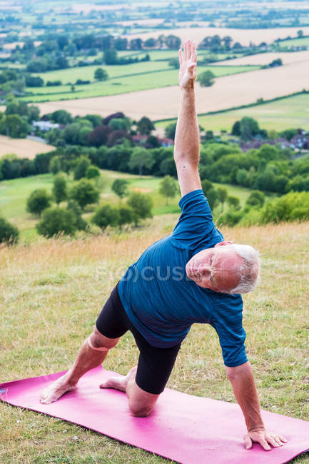 Senior man taking part in outdoor yoga class on a hillside. — Stock Photo