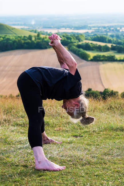 Femme âgée prenant part à un cours de yoga en plein air sur la colline . — Photo de stock