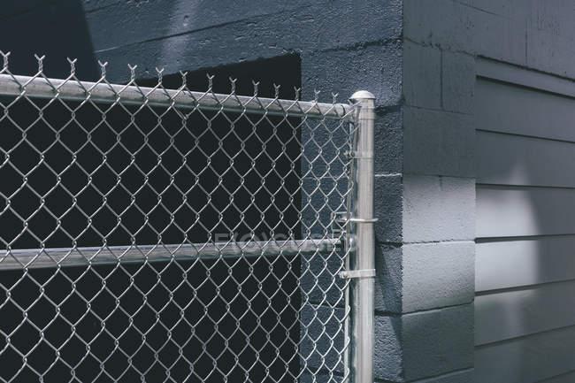 Цепной забор над дверью здания через серую городскую стену — стоковое фото