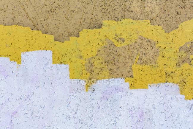 Revêtement de peinture jaune, blanche et brune sur le mur du bâtiment — Photo de stock