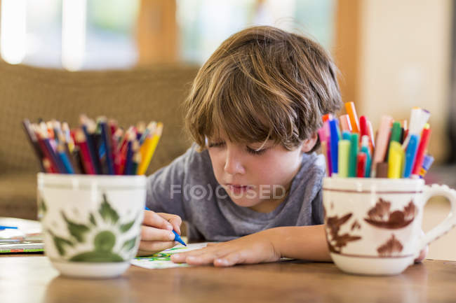 Little boy drawing with colorful pens at desk — Stock Photo