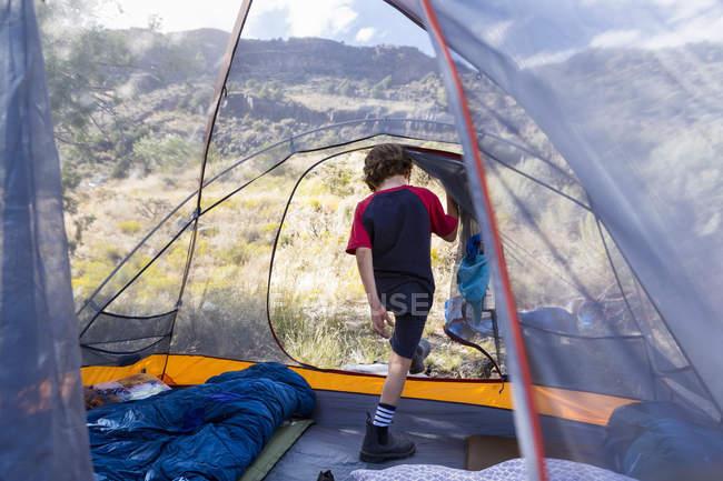 Age primaire garçon sortant tente tôt le matin lumière — Photo de stock