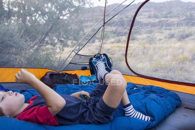 Menino pré-adolescente deitado na tenda na natureza — Fotografia de Stock
