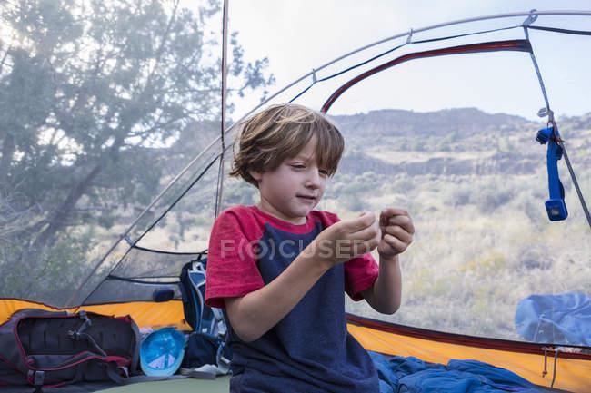 Petit garçon jouant dans une tente de voyage à l'extérieur — Photo de stock