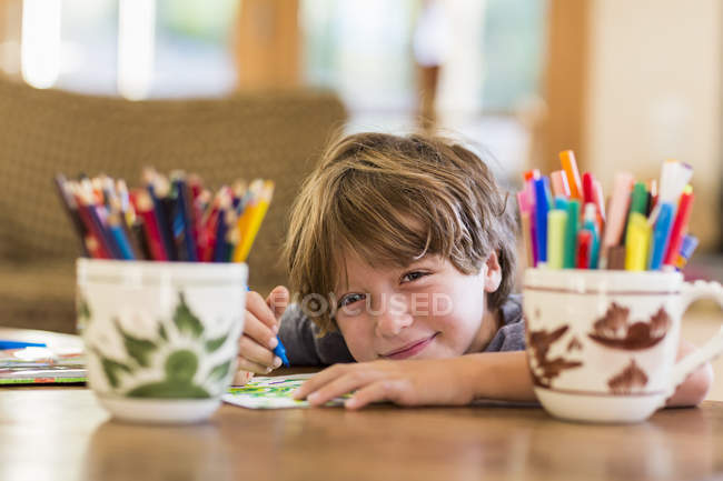 Elementary age boy drawing with various colorful pens — Stock Photo