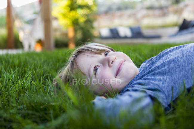 Portrait of smiling elementary age boy lying down in green grass — Stock Photo