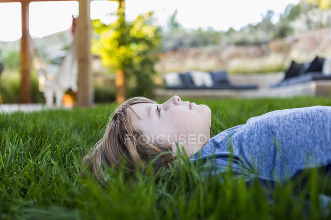 Portrait of smiling pre-teen boy lying down in green grass — Stock Photo