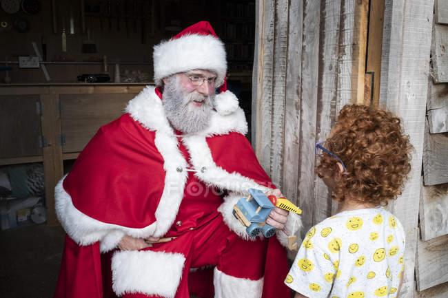 Чоловік у костюмі Миколая, який дарує хлопцеві дерев'яну іграшкову машину з рудим кучерявим волоссям.. — стокове фото