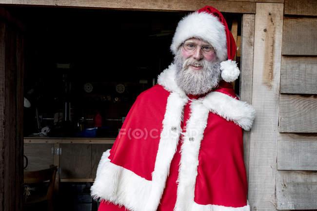 Чоловік у костюмі Санта Клауса стоїть у дверях майстерні, дивлячись у камеру.. — стокове фото