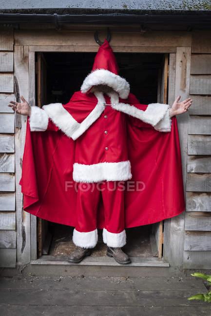 Чоловік у костюмі Миколая стоїть у дверях майстерні.. — стокове фото