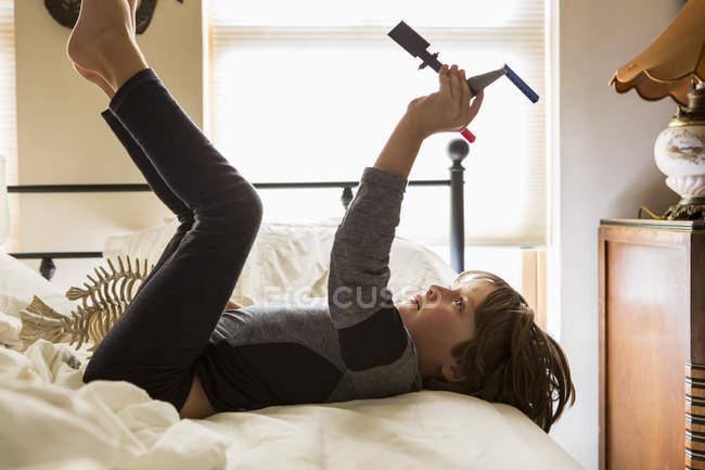 Élémentaire âge garçon jouer avec jouet sur lit à la maison — Photo de stock