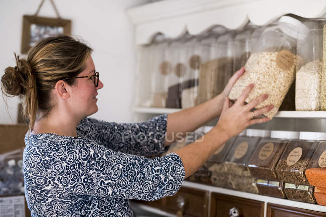 Woman standing in a kitchen, placing jars with oats onto a shelf. — Stock Photo