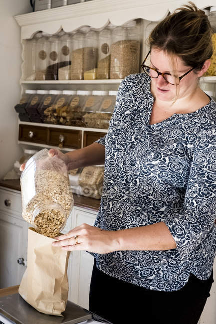 Woman standing in kitchen, pouring oats into paper bag. — Stock Photo