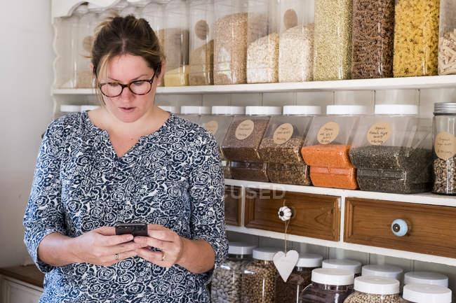 Жінка стоїть на кухні, користуючись мобільним телефоном.. — стокове фото
