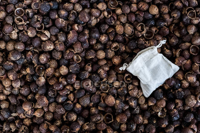 High angle close-up of dried brown soap nuts and reusable bag, full frame. — Stock Photo