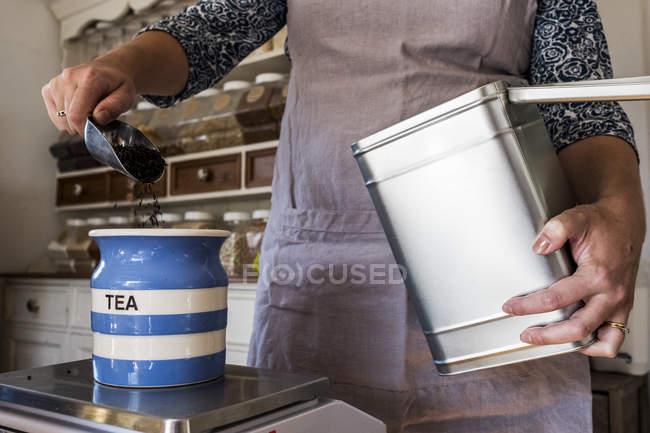 Close-up de mulher de pé em uma cozinha, colocando chá solto em frasco de cerâmica azul listrado. — Fotografia de Stock