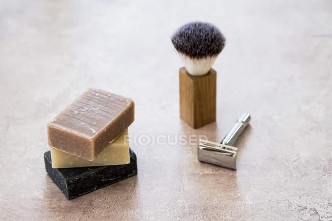 Primer plano de ángulo alto de barras apiladas caseras de jabón, cepillo de afeitar y afeitadora . - foto de stock