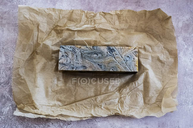 High angle close-up of homemade bar of soap on brown paper. — Stock Photo