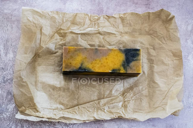 High angle close-up of yellow and black homemade bar of soap on brown paper. — Stock Photo