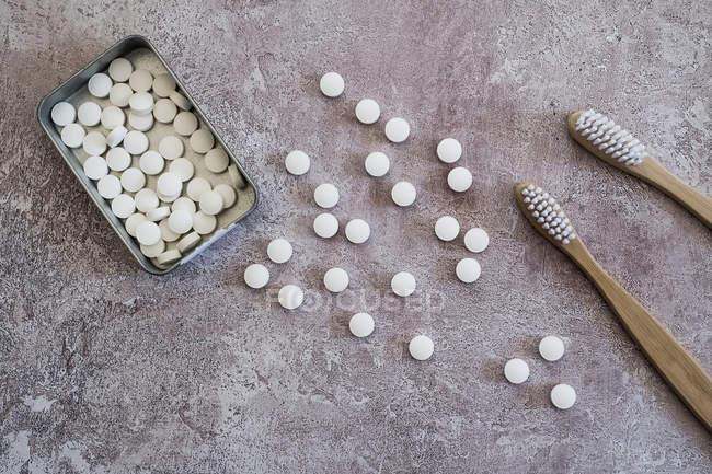 Primo piano ad alto angolo di spazzolini da denti in legno e pillole di sapone in scatola metallica . — Foto stock