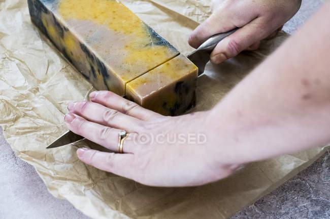 Alto ángulo de primer plano de las manos femeninas de corte amarillo y negro barra casera de jabón con cuchillo de cocina . - foto de stock