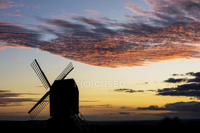 Moulin à vent au coucher du soleil sous un ciel nuageux et romantique. — Photo de stock