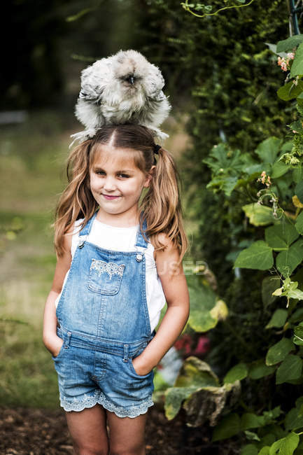 Smiling blonde girl standing in garden, with fluffy grey chicken on head. — Stock Photo