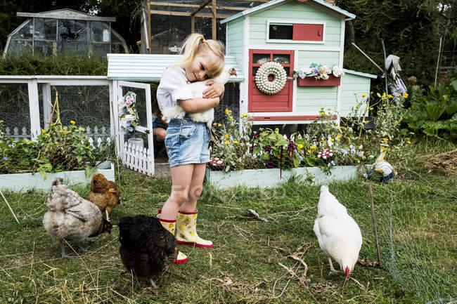 Блондинка, стоящая в саду перед курятником с белой курицей . — стоковое фото