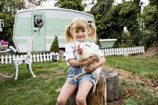 Blonde girl sitting in garden holding white chicken near white and green retro caravan. — Stock Photo