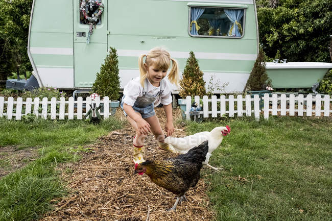 Blonde girl with chickens on garden path by white and green retro caravan. — Stock Photo