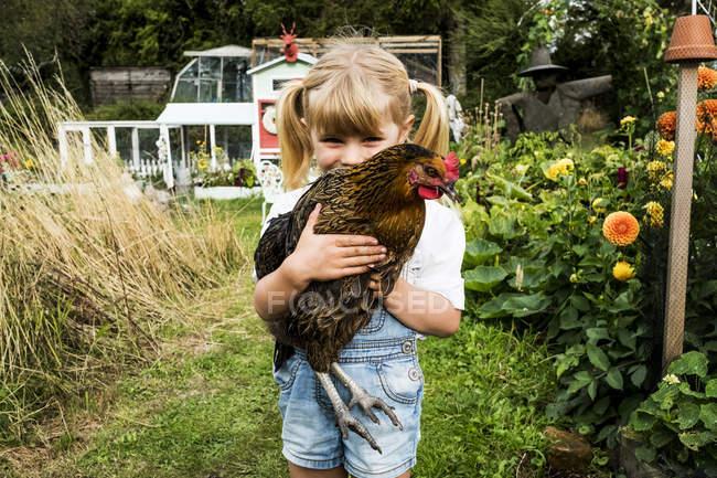 Ragazza bionda in piedi in giardino, con in mano pollo marrone . — Foto stock