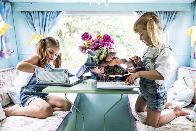 Duas garotas sentadas à mesa dentro da caravana azul e brincando . — Fotografia de Stock