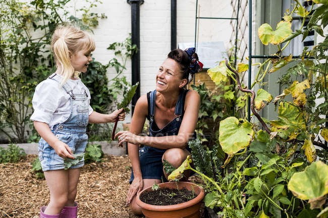 Smiling woman and girl in garden, picking fresh vegetables. — Stock Photo
