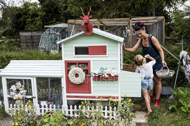 Smiling woman and girl standing in garden next to colorful hen house. — Stock Photo
