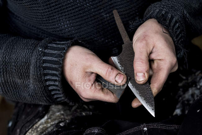 High angle close-up of hands of person working on handmade knife using piece of sandpaper. — Stock Photo