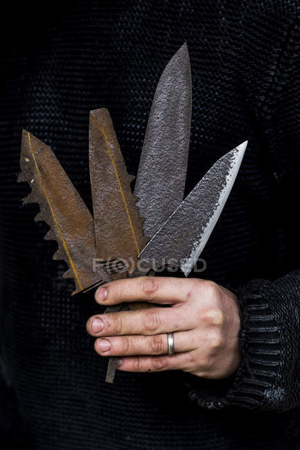 Close-up of person holding a selection of partially rusted and serrated knife blades. — Stock Photo